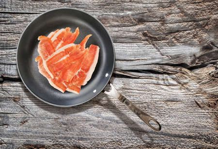 teflon: Dry Cured Smoked Pork Ham Slices, in Teflon Frying Pan, on Old, Weathered, Cracked, Wooden Table Surface.
