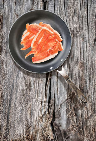 fryingpan: Dry Cured Smoked Pork Ham Slices, in Teflon Frying Pan, on Old, Weathered, Cracked, Wooden Table Surface.