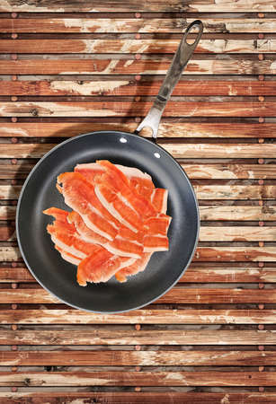 fryingpan: Smoked Prosciutto Ham Slices, in Teflon Frying Pan, on Old Weathered Peeled off Wooden Place Mat. Stock Photo