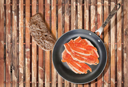 peeled off: Smoked Prosciutto Ham Slices in Teflon Frying Pan with Slice of Bread on Old Weathered Peeled off Wooden Place Mat. Stock Photo