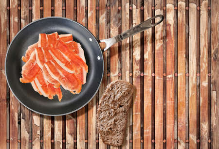 fryingpan: Smoked Prosciutto Ham Slices in Teflon Frying Pan with Slice of Bread on Old Weathered Peeled off Wooden Place Mat. Stock Photo