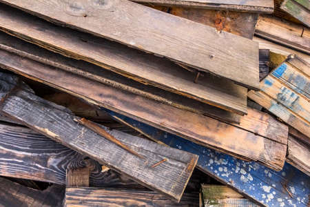 disposed: Photograph of old, rotten, scrapped floorboards and decking planks amassed and scattered in a untidy heap. Stock Photo