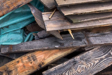 softwood: Heap of Old Scrapped Rotten Floorboards with folded Blue Plastic Foil. Stock Photo