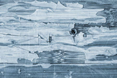 drilled: Photograph of Blue stained, old, weathered, varnished wooden laminated panel, cracked, scratched grunge texture.