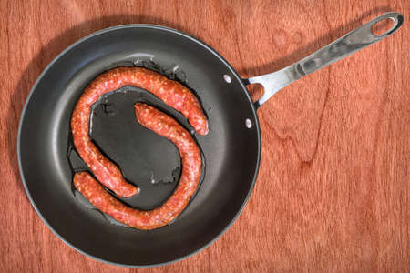 fryingpan: Raw Homemade Sausages in Teflon Frying Pan on Wooden Background