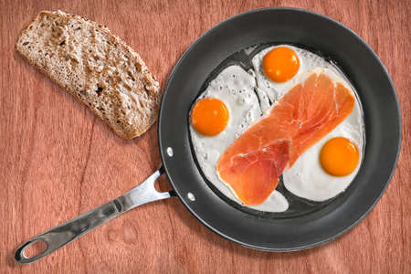 fryingpan: Fried Eggs and Smoked Ham Rasher in Frying Pan with Slice of Bread on Cherry Wood Background Stock Photo