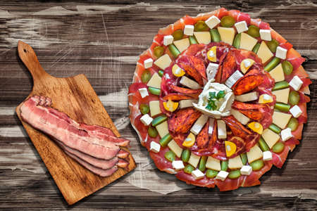 plateful: Plateful of Appetizer Meze with Bacon Rashers on Cutting Board Placed on Old Wood Background Stock Photo