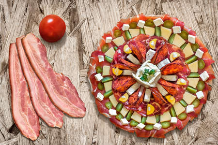 plateful: Plateful of Appetizer Meze with Bacon Rashers and Tomato on Chipboard Background