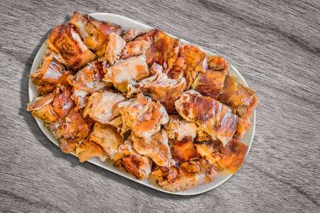 plateful: Plateful of Spit Roasted Pork Slices on Old Wooden Background