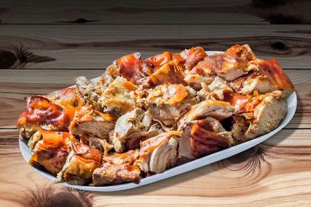 plateful: Plateful of Spit Roasted Pork Slices on Wood Background