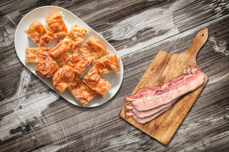 peeledoff: Platter of Cheese Pie Gibanica and Cutting Board with Pork Bacon Rashers Set on Old Wooden Garden Table Surface