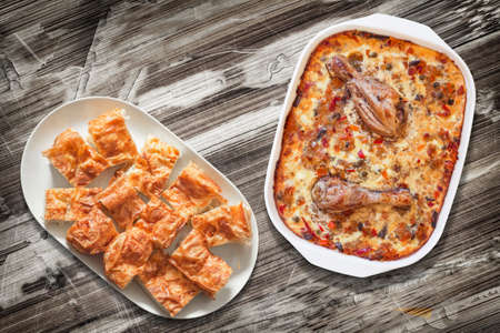 peeledoff: Chicken Meat with Vegetable Stew and Gibanica Cheese Pie Slices in Platters on Old Wooden Garden Table Surface