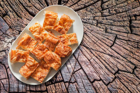 plateful: Plateful of Serbian Cheese Pie Gibanica on Old Cracked Stump Surface Stock Photo
