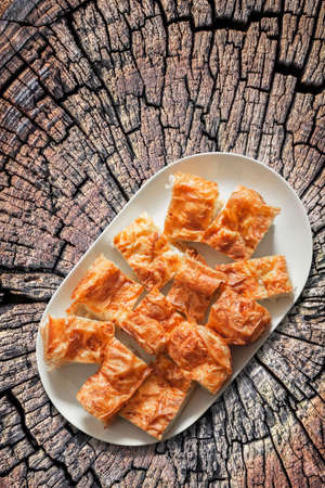 serbian: Plateful of Serbian Cheese Pie Gibanica on Old Cracked Stump Surface Stock Photo