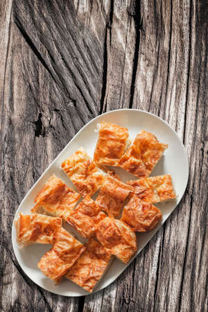 plateful: Plateful of Serbian Cheese Pie Gibanica on Old Wooden Garden Table Surface