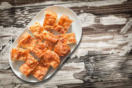 plateful: Plateful of Serbian Cheese Pie Gibanica on Old Peeled Off Wood Surface