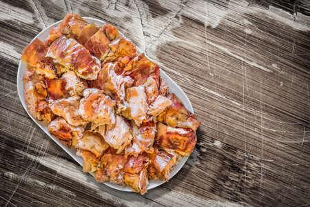 peeledoff: Plateful of Spit Roasted Pork Slices on Old Cracked Peeled Wooden Surface