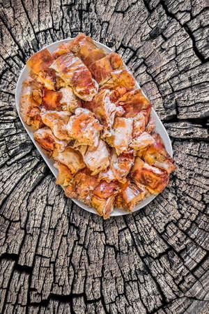 plateful: Plateful of Spit Roasted Pork Slices on Old Cracked Stump Surface