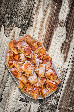 peeledoff: Plateful of Spit Roasted Pork Slices on Old Cracked Peeled Wooden Surface