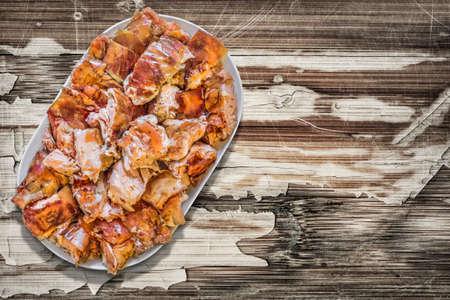 plateful: Plateful of Spit Roasted Pork Slices on Old Cracked Peeled Wooden Surface