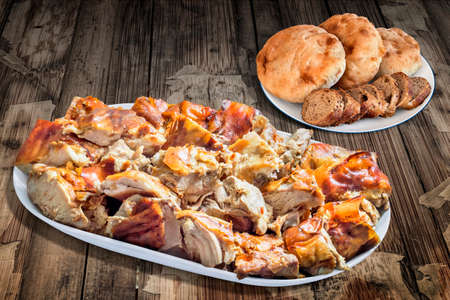 integral: Plateful of Spit Roasted Pork with Baguette Integral Bread Slices and Pita Bread Loafs on Old Wooden Table Stock Photo