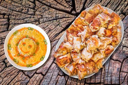 ensalada rusa: Plateful de Spit asado de cerdo con plato de ensalada rusa en el viejo toc�n agrietado superficie Foto de archivo