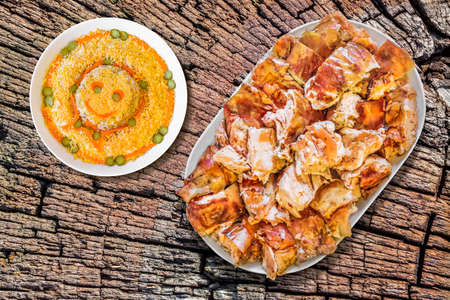 ensalada rusa: Plateful de Spit asado de cerdo con plato de ensalada rusa en el viejo tocón agrietado superficie Foto de archivo