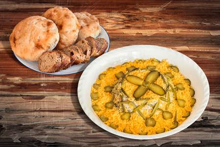 russian salad: Ensalada rusa Adornado con Baguette Integral rebanadas de pan y pan de pita Panes en mesa de madera Foto de archivo