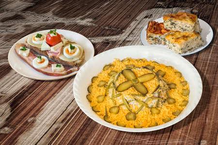 ensalada rusa: Ensalada rusa con tocino huevo y queso sándwich de queso y espinacas Pie Zeljanica en mesa de madera vieja