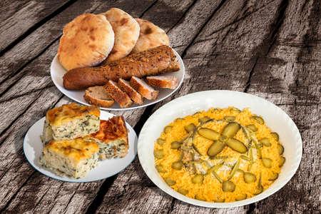 ensalada rusa: Ensalada rusa con la empanada de pan Panes y Espinacas Queso en agrietada vieja mesa de madera