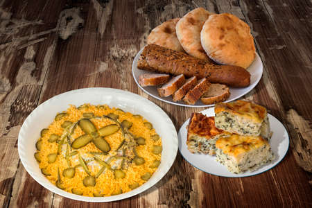 Russian Salad with Bread Loafs and Spinach Cheese Pie on Old Cracked Wooden Table