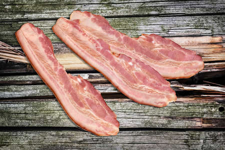 streaky: Pork Bacon Rashers on Old Knotted Cracked Wood Background