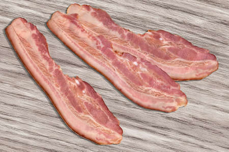 bleached: Pork Bacon Rashers on Bleached Wood Background