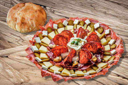 plateful: Plateful of Serbian Appetizer Meze with domestic Pita Bread, on Rough Chipboard Surface