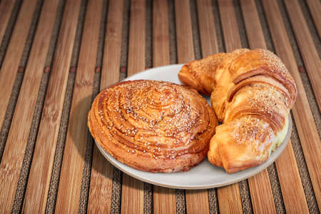 boulangerie: Croissant Puff Pastry Snail Rolls Sprinkled with Sesame Seeds on Bamboo Place Mat
