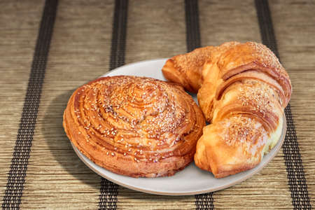 sprinkled: Croissant Puff Pastry Snail Rolls Sprinkled with Sesame Seeds on Parchment Plated Place Mat
