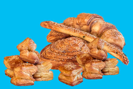boulangerie: Bunch of Croissant Puff Pastry Sprinkled with Sesame Seeds, Isolated on Blue Background.