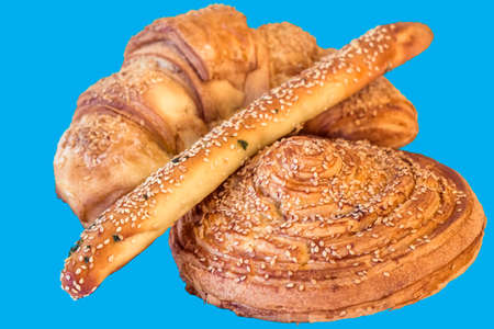 boulangerie: Croissant Puff Pastry Sprinkled with Sesame Seeds, Isolated on Blue Background. Stock Photo