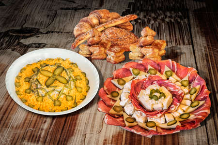 peeledoff: Olivier Salad with Appetizer Dish Meze and Sesame Croissant Puff Pastry on Old Cracked Wooden Table. Stock Photo