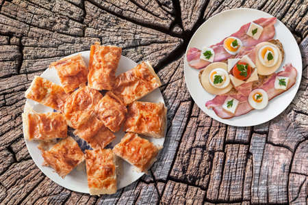 plateful: Plateful of Serbian Gibanica Cheese Crumpled Pie with Plate of Bacon, Cheese, Egg, Ham and Cherry Tomato Sandwich on Old Cracked Stump Picnic Table