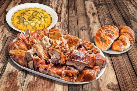 russian salad: Plato de Asado al pincho de cerdo con ensalada rusa y croissant pasta de hojaldre en la vieja mesa de jardín de madera Foto de archivo