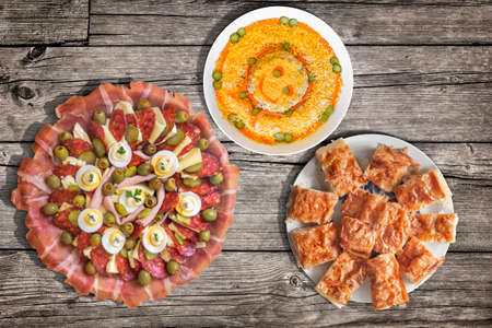 plateful: Plateful of Serbian Traditional Appetizer Meze with Gibanica Crumpled Cheese Pie and Garnished Olivier Salad Set on Old Wooden Picnic Table Stock Photo