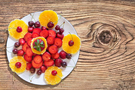 plateful: Plateful of Orange and Strawberries Slices with Cherries on Old Knotted Wooden Garden Table