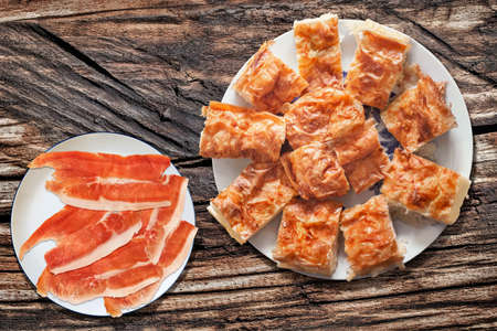 plateful: Plateful of Gibanica Crumpled Cheese Pie with Smoked Pork Ham Prosciutto Slices on Old Picnic Wooden Table Stock Photo