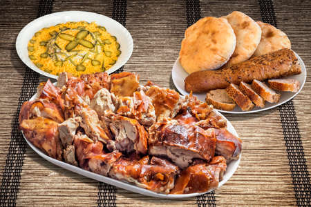 plateful: Plateful of Spit Roasted Pork with Russian Salad and Baguette Integral Bread with Pita Bread Loafs on Woven  Parchment Place Mat
