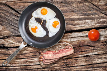 teflon: Fried Eggs in Teflon Frying Pan with Plate of Bacon Rashers Sandwich and Tomato on Old Wooden Picnic Table