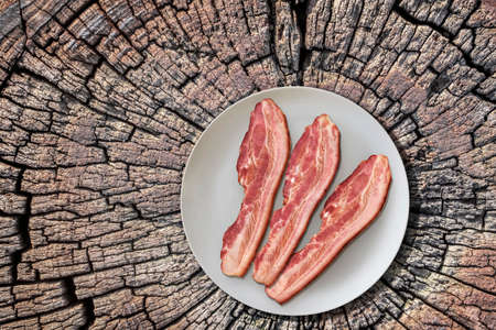 plateful: Plateful of Three Pork Belly Bacon Rashers on Old Cracked Stump Picnic Table Stock Photo