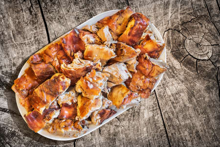plateful: Plateful of Spit Roasted Pork Slices on Old Wooden Picnic Table