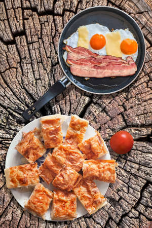 teflon: Fried Eggs and Bacon Rashers in Teflon Frying Pan with Tomato and Plateful of Gibanica Cheese Pie Slices Set on Old Cracked Stump Picnic Table