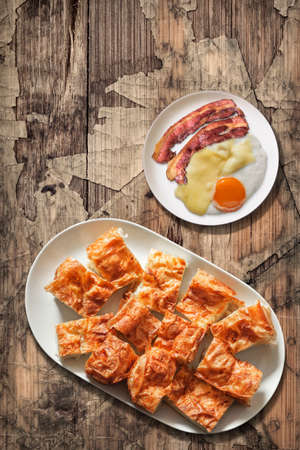 plateful: Plateful of Gibanica Crumpled Cheese Pie with Plate of Fried Egg and Bacon Rashers Set on Old Wooden Garden Table Stock Photo